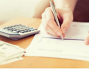 Image shows a person filling in forms with a calculator to hand. They could be researching bad credit loans.