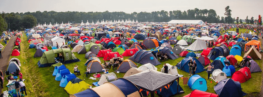 Image shows lots of tents set up in a field for a festival