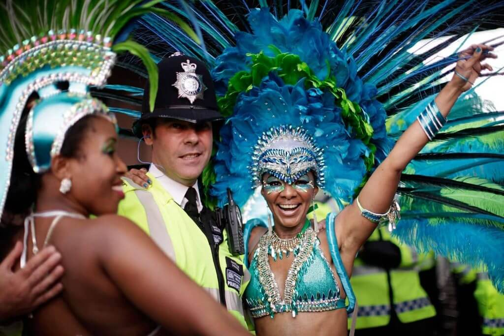 Image shows a police officer having fun with two brightly dressed festival dancers
