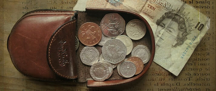 Image shows a leather change wallet with coins and notes ready for a festival