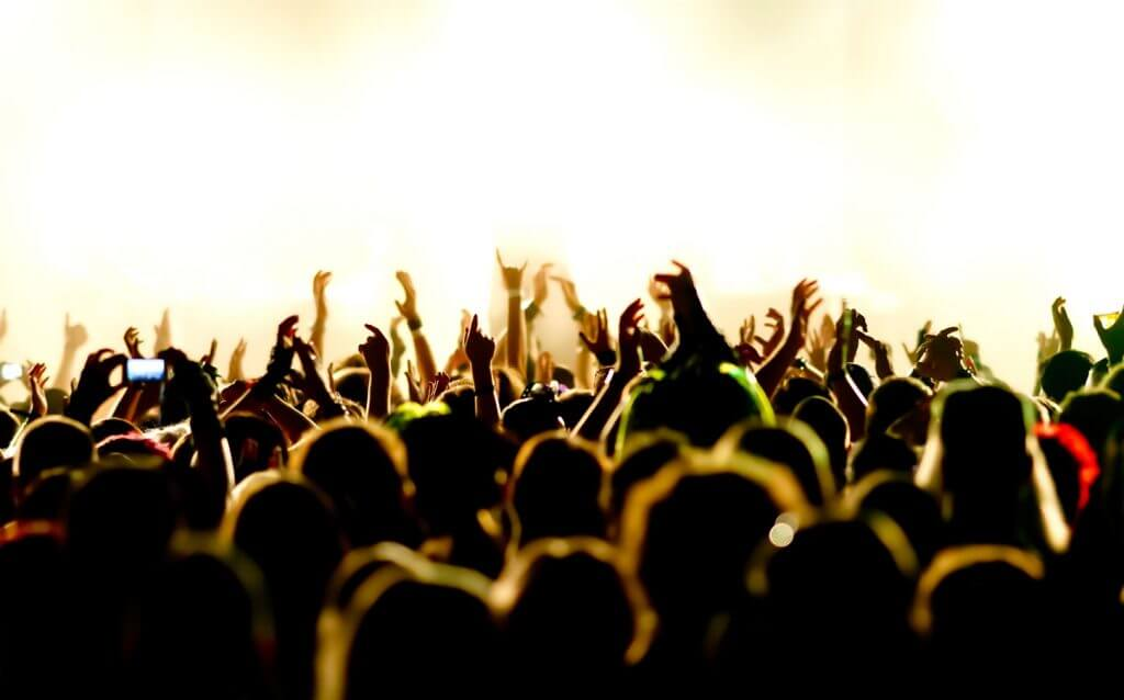 Image shows a crowd of festival revelers in front of a stage