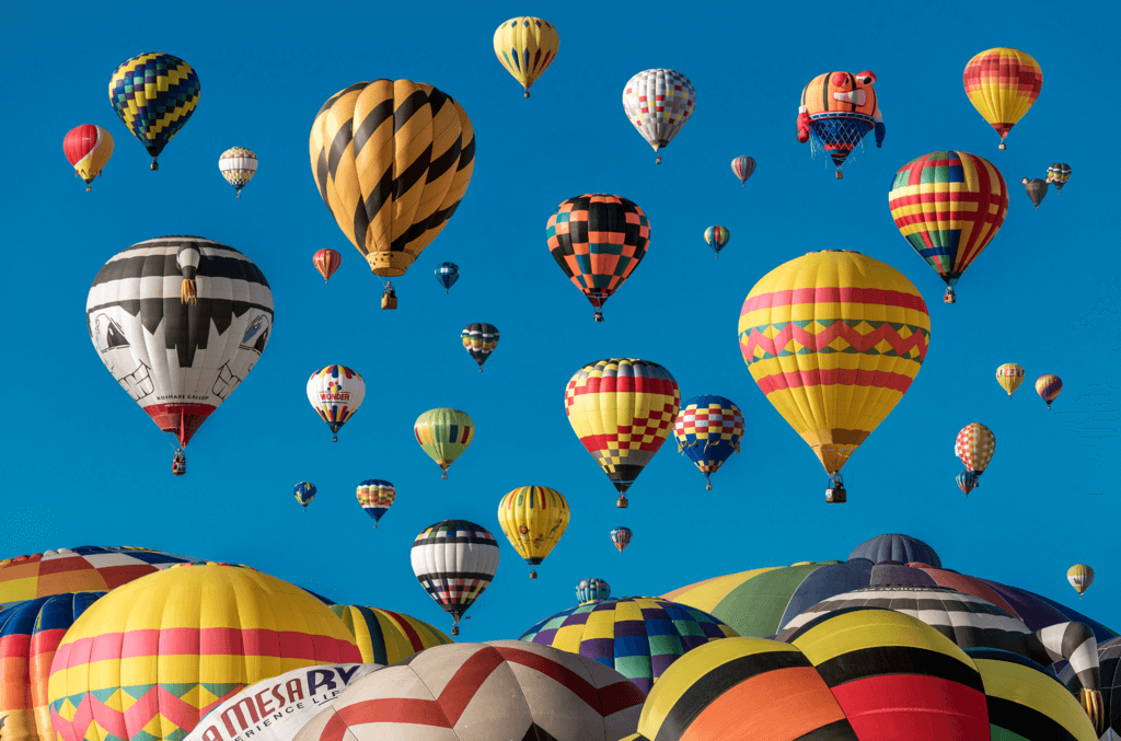 Image shows scores of hot air balloons setting off at a festival